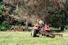 Meadow mowing. Farm tractor mowing meadow grass Royalty Free Stock Photo
