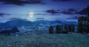 Meadow near the village in mountain valley at night Stock Images