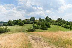 Meadow and parkland at the Divoka Sarka in Prague. View of a footpath, dry meadow, parkland and cloudy sky on a sunny day at Divoka Sarka. It`s a nature reserve Royalty Free Stock Images