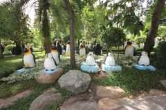 A meadow with penguins and grass and trees and stones in the Nong Nooch tropical botanic garden near Pattaya city in Thailand Royalty Free Stock Image