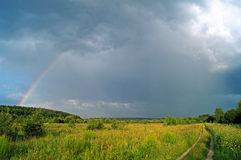 Meadow with rainbow after the rain. Stock Images