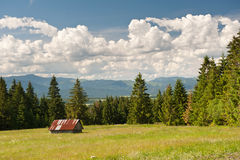 Meadow in summer with small white house, Low Tatras and cloudy sky. Royalty Free Stock Photography