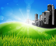 Meadow with sunlight and city at the background. Stock Image