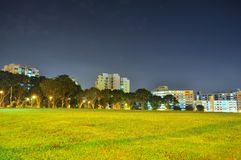 Meadow with trees and residential buildings in the background Stock Photos