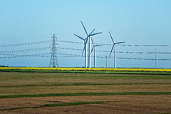 Meadow with Wind turbines generating electricity and electric po. Meadow with Wind mill turbines generating electricity and electric power lines, in England, the royalty free stock photo