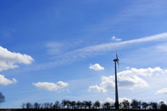 Meadow with Wind turbines generating electricity  trees and skys Royalty Free Stock Photo