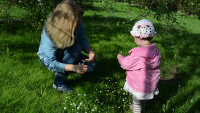 Meadow wreath. Mother and daughter the garden meadow weave a small wreath of daisies stock footage