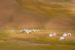 Meadow with yurts of the nomads in Central Asia. Asian yurts of the nomads on the beautiful mountain meadow in Kyrgyzstan. Kyrgyzstan's population is 5.2 million Stock Image