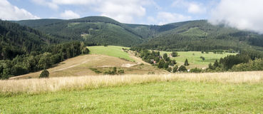 Meadows and fields with Kralicky Sneznik mountain range with clouds above Royalty Free Stock Photos