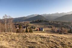 Meadows and mountains and several houses Royalty Free Stock Photography