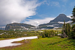 Meadows, mountains, snow, and clouds Royalty Free Stock Images