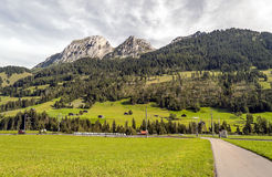 Meadows with wooden houses. In Switzerland. Alpine mountains in the background are on a cloudy day Stock Photo