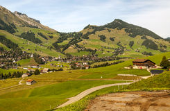 Meadows with wooden houses. In Switzerland. Alpine mountains in the background are on a cloudy day Royalty Free Stock Photography