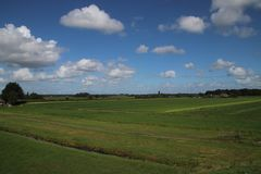 Meadows of the Zuidplaspolder at Moordrecht, the lowest area of western europe. In the Netherlands in wide area view with blue sky and white clouds stock images