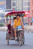 Meager man on a rickshaw with passenger, Beijing, China. BEIJING-JULY 10, 2015. Rickshaw with a passenger. In Chinese cities rickshaws are still a popular and Stock Photos