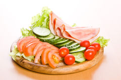 Meal. Fresh ham & salad on a wooden plate Stock Images