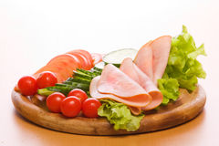Meal. Fresh ham & salad on a wooden plate Stock Image