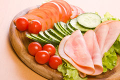 Meal. Fresh ham & salad on a wooden plate Stock Photography