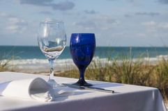 Meal on the beach. A table set for a meal on the beach with waves in the background Stock Photo