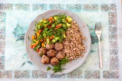 Photo of a traditional Russian meal - meat, buckwheat and vegetables royalty free stock photography