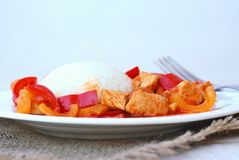 Meal from chicken meat with Indian spices, green and red pepper and rice on white plate, gunny cloth and wood with fork Stock Photos