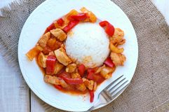 Meal from chicken meat with Indian spices, green and red pepper and rice on white plate, gunny cloth and wood with fork Royalty Free Stock Photo