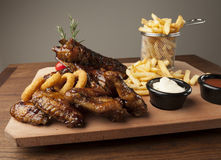 Meal of chicken wings and ribs with fries Royalty Free Stock Images