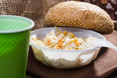 Meal in disposable cutlery. Closeup still life disposable green cup white fork and cabbage and corn salad wheat bun topped with sesame seeds lying on brown brat Stock Image