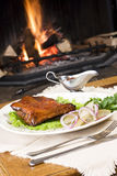 Meal by fireplace. Meal of meat with vegetables and garnishments on a white plate, sitting on a table in front of a burning fireplace Stock Photo
