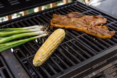 The Meal on the Grill. A piece of Steak with scallions and corn Royalty Free Stock Photography