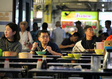 Meal in a hawkers center. SINGAPORE/SINGAPORE - CIRCA NOVEMBER 2015: People having a meal in a hawkers center stall in Singapore's Chinatown royalty free stock images