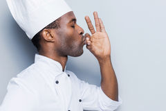 This meal is just perfect!. Side view of confident young African chef in white uniform keeping eyes closed and gesturing while standing against grey background Stock Photography