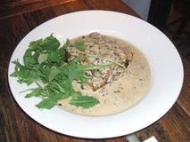 Meal of lasagne, mushrooms, salad, and cream sauce. Stock Image