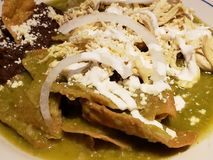 chilaquiles dish in green sauce with refried beans, typical mexican food royalty free stock photography