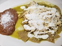 chilaquiles dish in green sauce with refried beans, typical mexican food stock photography
