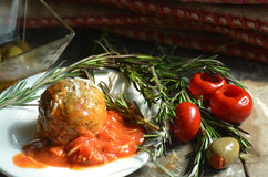 Meal of Meatball and tomato sauce served on plate garnished with Rosemary sprigs and antipasto. Tabletop view of meatball, sauce, Rosemary springs and antipasto Royalty Free Stock Images