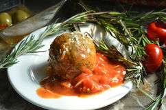 Meal of Meatball and tomato sauce served on plate garnished with Rosemary sprigs and antipasto. Tabletop view of meatball, sauce, Rosemary springs and antipasto Stock Photo
