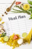 Meal Plan and Products. A meal plan for a week on a white table among products for cooking - pastas, basil, vegetables, lime, seeds, nuts and spices. Top view stock photography