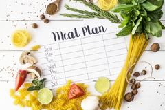 Meal Plan and Products. A meal plan for a week on a white table among products for cooking - pastas, basil, vegetables, lime, seeds, nuts and spices. Top view royalty free stock images