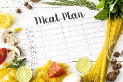 Meal Plan and Products. A meal plan for a week on a white table among products for cooking - pastas, basil, vegetables, lime, seeds, nuts and spices. Top view stock photos