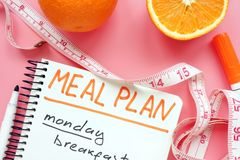 Meal plan for weight loss with orange on pink surface. Meal plan for weight loss with orange on the pink surface stock photos