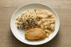 Pork chop, Brown rice and white beans. White dish on wooden tabl Royalty Free Stock Image