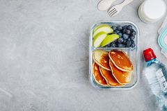 Meal prep containers with pancakes, blueberry and apple. Breakfast in lunch box. Top view. Copy space royalty free stock photos