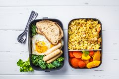 Meal prep containers with rice with chicken, baked vegetables, e. Ggs, sausages and salad for breakfast and lunch overhead shot, copy space, wtite wooden stock photos