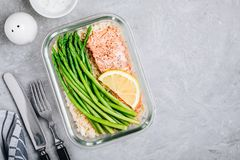 Meal prep lunch box container with baked salmon fish, rice, green asparagus royalty free stock photos