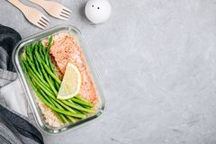 Meal prep lunch box container with baked salmon fish, rice, green asparagus royalty free stock images
