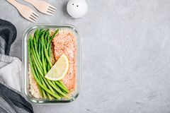 Meal prep lunch box container with baked salmon fish, rice, green asparagus stock image