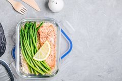Meal prep lunch box container with baked salmon fish, rice, green asparagus royalty free stock photography