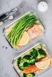 Meal prep lunch box containers with baked salmon fish, rice, green broccoli and asparagus stock images