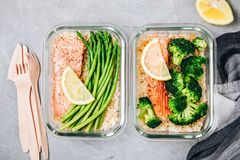 Meal prep lunch box containers with baked salmon fish, rice, green broccoli and asparagus stock photos
